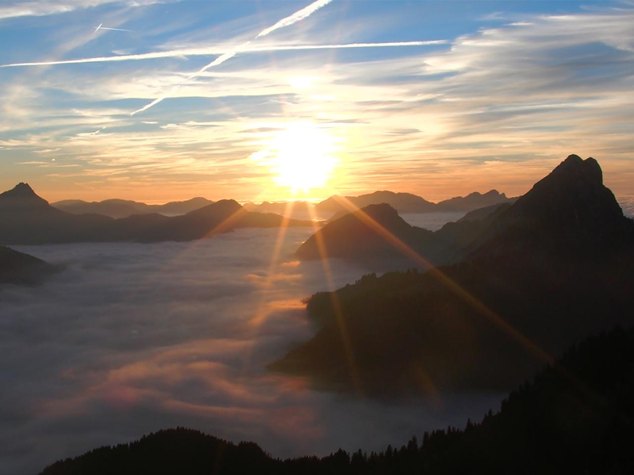 Omgeving - Ondergaande zon boven wolken