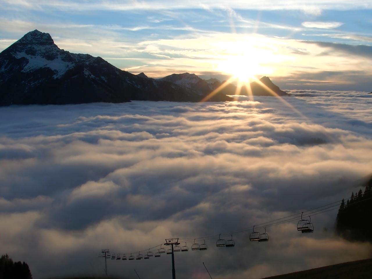 Omgeving - Ondergaande zon met skilift en wolken